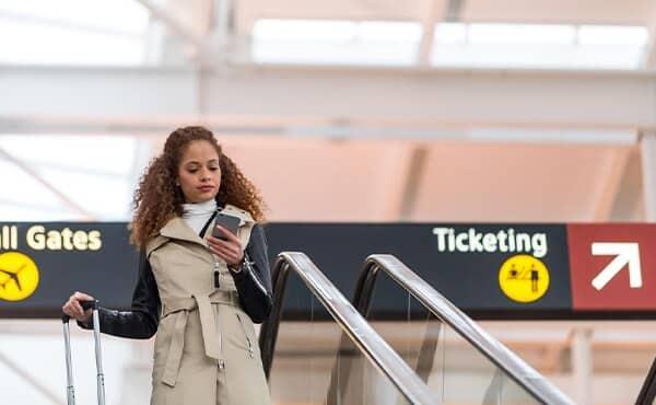 woman walking through airport looking at phone